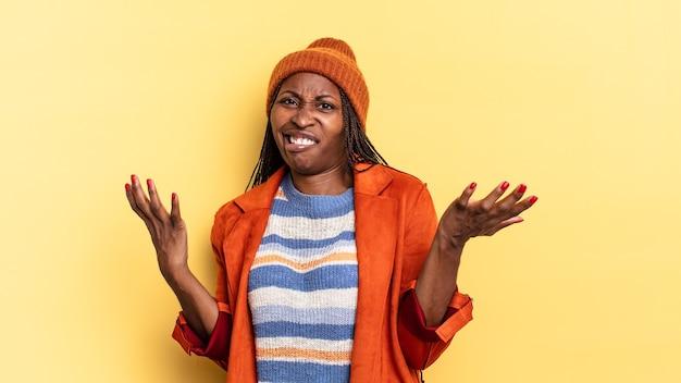 Afroschwarze hübsche frau, die mit einem dummen, verrückten, verwirrten, verwirrten ausdruck die achseln zuckt und sich genervt und ahnungslos fühlt