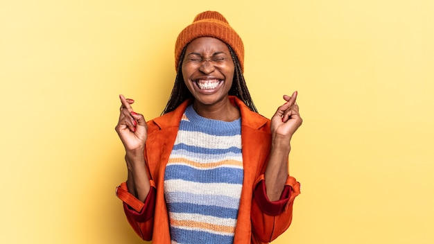 Afroschwarze hübsche frau, die nervös und hoffnungsvoll ist, die daumen drückt, betet und auf viel glück hofft