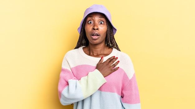 Afroschwarze hübsche frau, die sich schockiert und überrascht fühlt, lächelt, sich die hand zu herzen nimmt, glücklich ist, diejenige zu sein oder dankbarkeit zu zeigen