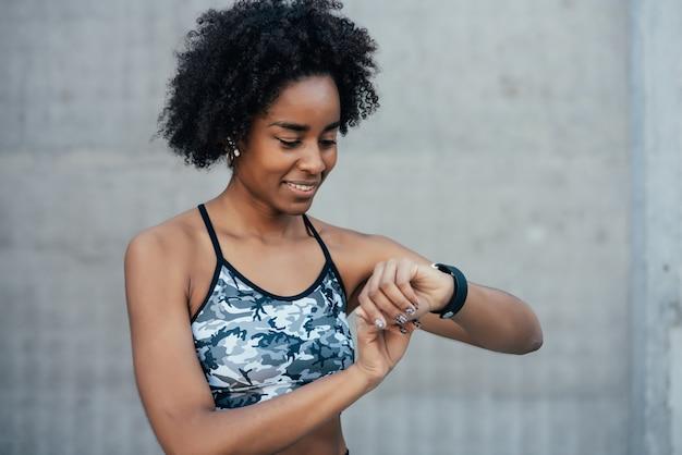 Afrosportliche frau, die die zeit auf ihrer smartwatch überprüft, während sie im freien trainiert