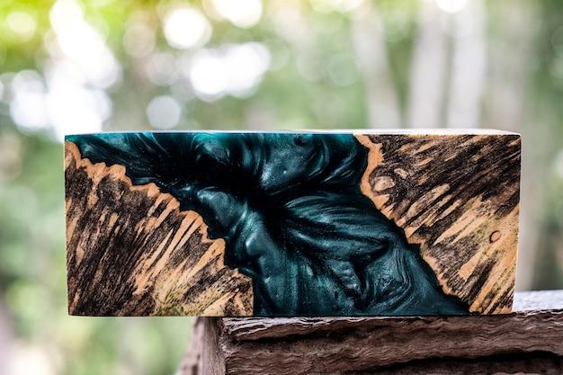 Afzelia wurzelholzbarrenguss mit epoxidharz stabilisierend für rohlinge auf unscharfem hintergrund