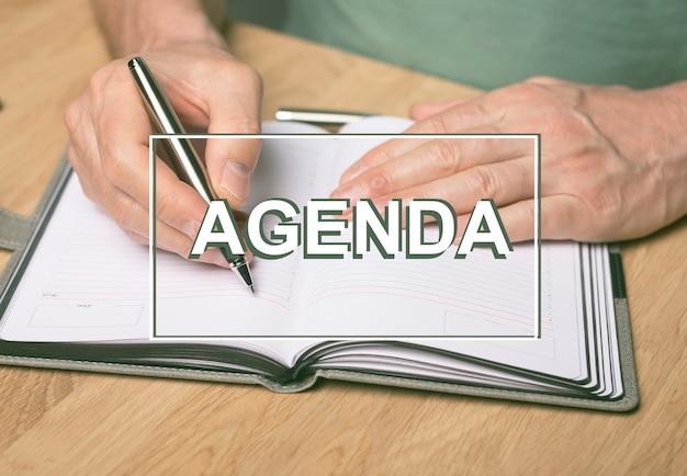 Agenda-wort. beschriftung auf dem foto von händen, die im planer oder organisator schreiben.