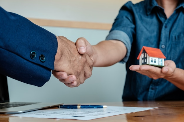 Agenten geben hausschlüssel von kunden und halten us-dollar bank im büro der agentur.