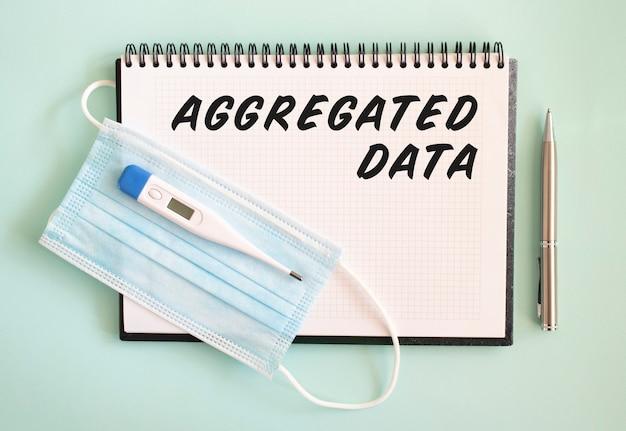 Aggregated data text in einem notizbuch mit einer gesichtsmaske und einem thermometer auf hellgrünem hintergrund