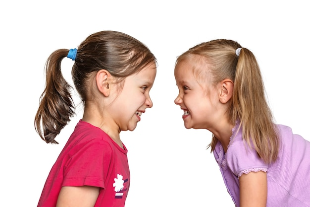 Aggression und streit zwischen zwei kleinen mädchen kinder streiten auf weißem hintergrund
