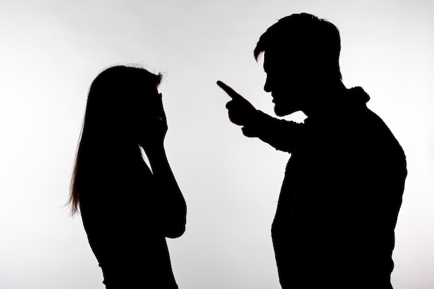 Aggressions- und missbrauchskonzept - mann und frau, die häusliche gewalt im studioschattenbild einzeln auf weißem hintergrund ausdrücken.