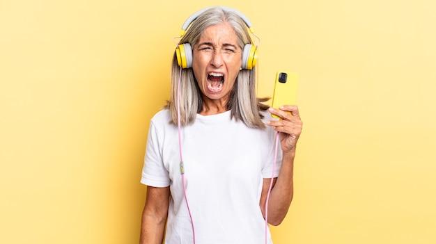 Aggressiv schreien, sehr wütend, frustriert, empört oder genervt aussehen, mit kopfhörern nein schreien