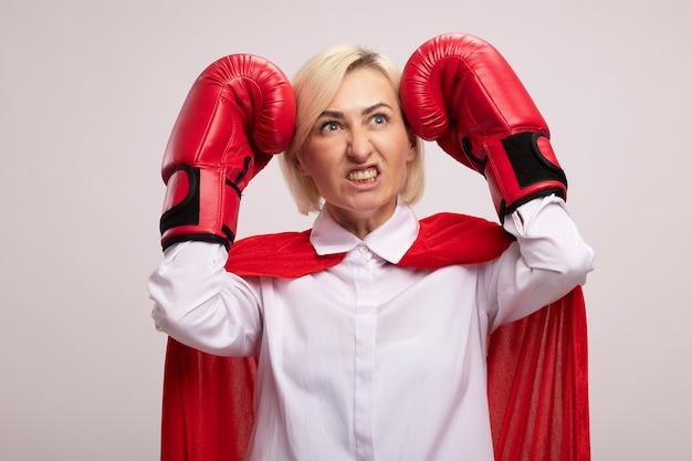 Aggressive blonde superheldin mittleren alters in rotem umhang mit boxhandschuhen, die den kopf mit fäusten berühren, die auf die seite schauen, die zähne zeigt
