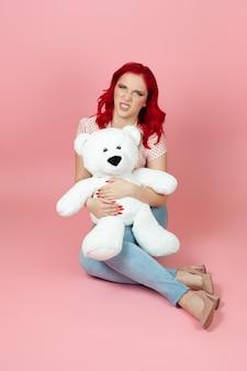 Aggressive, wütende frau, die einen großen weißen teddybär hält und ihre zähne entblößt