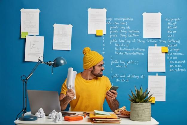 Aggressiver bärtiger mann hält zerknittertes papier, wütend, weil das projekt nicht funktionieren kann, hält smartphone, biss die zähne zusammen und schaut weg