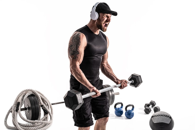 Aggressiver bärtiger starker muskulöser mann im sport- und kopfhörertraining mit langhantel auf weißem isolat.