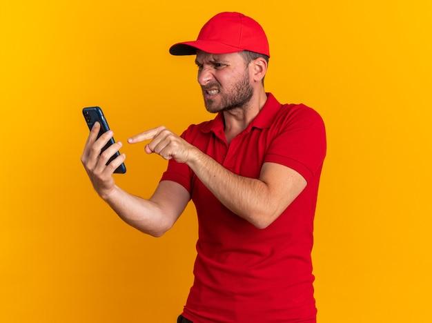 Aggressiver junger kaukasischer lieferbote in roter uniform und mütze, der das handy anschaut und zeigt