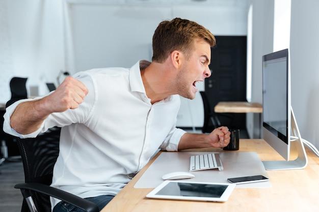 Aggressiver wütender junger geschäftsmann, der im büro mit computer schreit und arbeitet