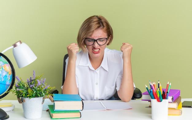 Aggressives junges blondes studentenmädchen mit brille sitzt am schreibtisch mit schulwerkzeugen, die fäuste mit geschlossenen augen ballen