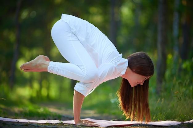 Agile frau steht auf hände in yoga-pose