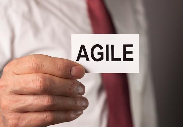 Agiles wort auf papier in der geschäftsmannhand business