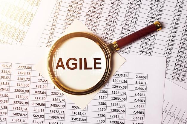 Agiles wort auf papieren durch vergrößerungsglas-geschäftskonzept