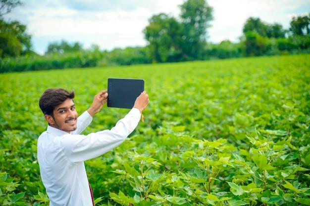 Agronom bei cotton field, zeigt einige informationen auf der registerkarte