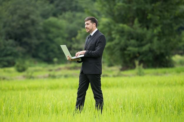 Agronom verwenden eines laptops zum lesen eines berichts und stehen auf einem landwirtschaftlichen gebiet.