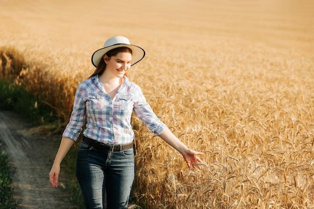 Agronomin mit hut studiert weizenernte im feld geschäftsfrau analysiert getreideernte...
