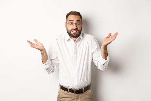 Ahnungslos besorgter manager zuckt die achseln, sieht verwirrt aus und steht