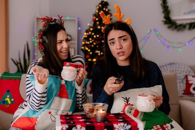 Ahnungslos hübsches junges mädchen mit stechpalmenkranz hält tasse und schaut auf ihre freundin, die tv-fernbedienung hält, die auf sessel-weihnachtszeit zu hause sitzt