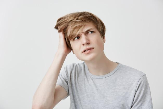 Ahnungslos verwirrter junger kaukasischer mann im grauen t-shirt, der mit verwirrtem und verwirrtem ausdruck beiseite schaut, kopf kratzt, versucht, sich an etwas wichtiges zu erinnern, vergaß den geburtstag seiner freundin