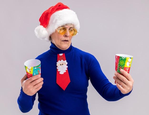 Ahnungslose ältere frau in sonnenbrille mit weihnachtsmütze und weihnachtskrawatte halten und betrachten pappbecher lokalisiert auf weißem hintergrund mit kopienraum