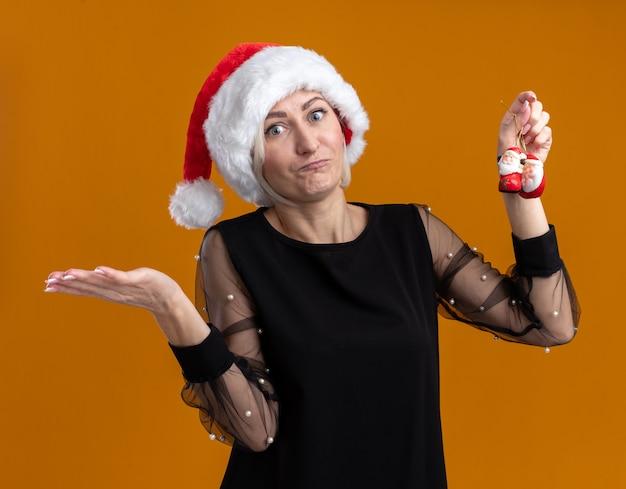 Ahnungslose blonde frau mittleren alters, die weihnachtsmütze trägt, die weihnachtsmannverzierungen des weihnachtsmanns hält, die leere hand lokalisiert auf orange wand zeigt