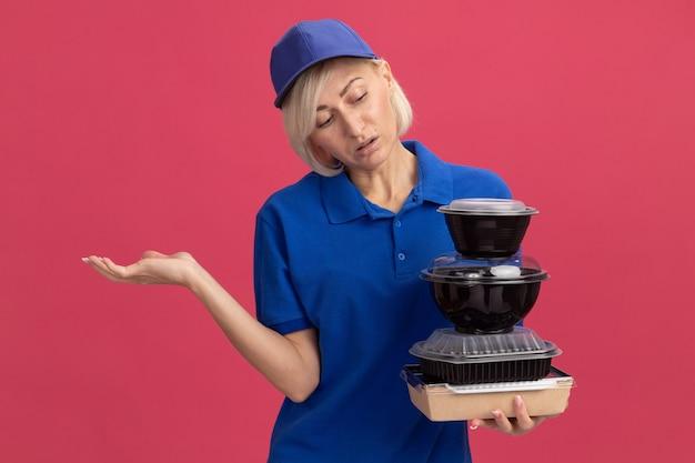Ahnungslose blonde lieferfrau mittleren alters in blauer uniform und mütze, die papiernahrungsmittelpakete und lebensmittelbehälter hält und sie mit leerer hand betrachtet