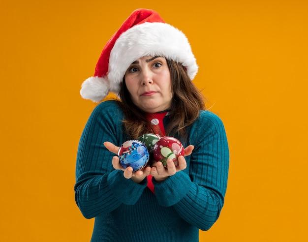Ahnungslose erwachsene kaukasische frau mit weihnachtsmütze und weihnachtsmann-krawatte, die glaskugelverzierungen einzeln auf orangefarbener wand mit kopienraum hält
