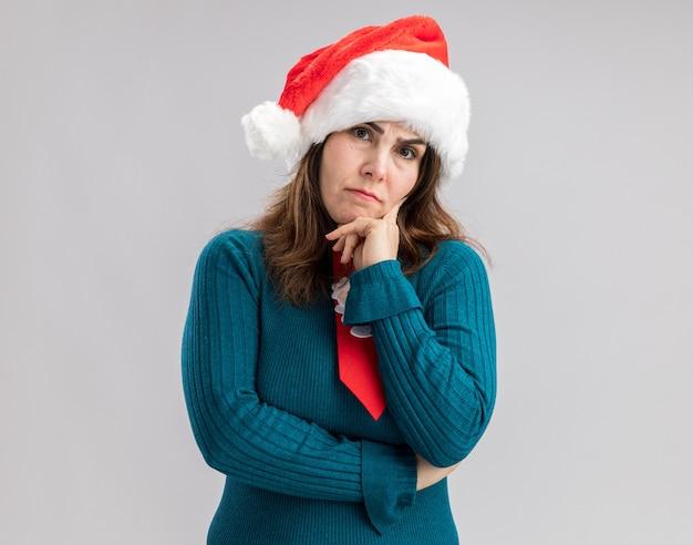 Ahnungslose erwachsene kaukasische frau mit weihnachtsmütze und weihnachtsmann-krawatte legt die hand auf das kinn, isoliert auf weißer wand mit kopierraum