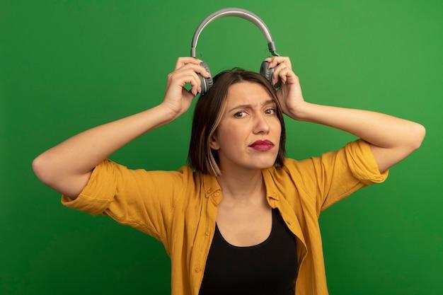 Ahnungslose hübsche kaukasische frau hält kopfhörer über kopf auf grün
