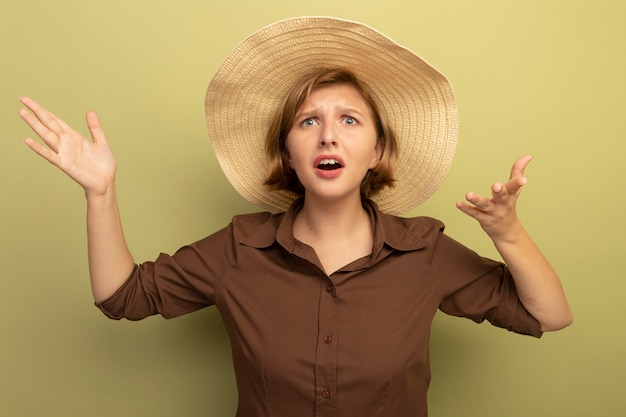 Ahnungslose junge blonde frau mit strandhut sieht gerade aus und zeigt leere hände