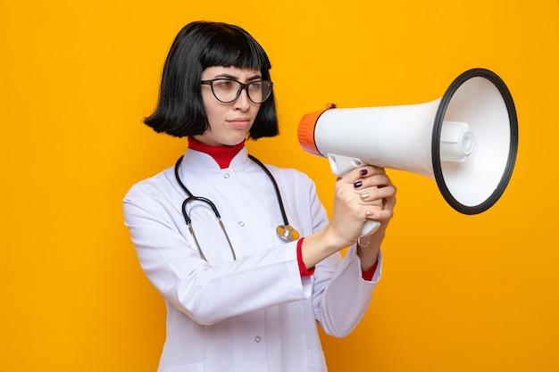 Ahnungslose junge hübsche kaukasische frau mit brille in arztuniform mit stethoskop, die lautsprecher hält und anschaut