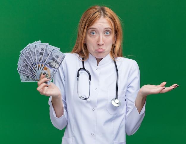 Ahnungslose junge ingwerärztin, die medizinisches gewand und stethoskop trägt und geld hält, das leere hand zeigt