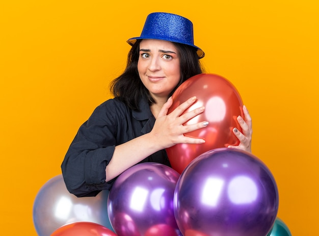 Ahnungslose junge kaukasische partyfrau mit partyhut, die hinter ballons steht und einen hält, der nach vorne isoliert auf oranger wand schaut