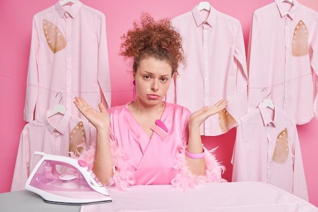 Ahnungslose lockige frau breitet palmen aus, fühlt sich zögerlich, hausarbeit trägt morgenmantel eisen gefaltete kleidung isoliert über rosa wand weiß nicht, was sie tun soll. zweifelnde hausfrau in der nähe des bügelbretts