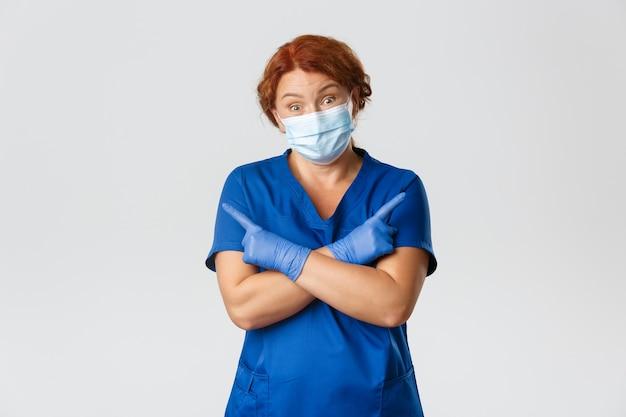 Ahnungslose rothaarige ärztin, krankenschwester in gesichtsmaske und gummihandschuhen wissen es nicht, zeigen zur seite und zucken verwirrt mit den schultern.