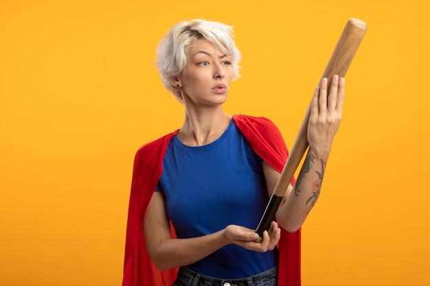 Ahnungslose superfrau mit rotem umhang hält und betrachtet baseballschläger isoliert auf orange wand