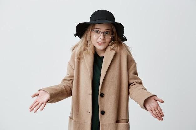 Ahnungslose, zweifelhafte, missfallene frau in mantel, brille und schwarzem hut zuckt unsicher mit den schultern und zögert, ob sie auf party oder verabredung geht. die zögernde junge frau weiß nicht, wie sie das zukünftige leben verändern kann
