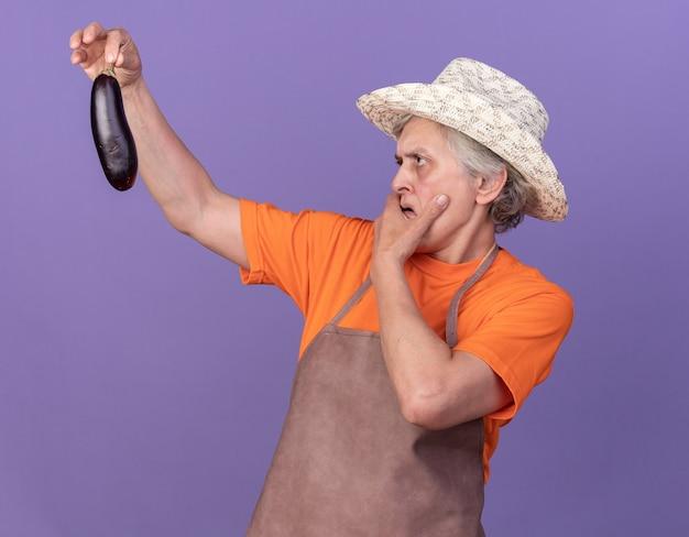 Ahnungsloser älterer weiblicher gärtner, der gartenhut trägt, setzt hand auf kinn, das aubergine auf purpur hält und betrachtet