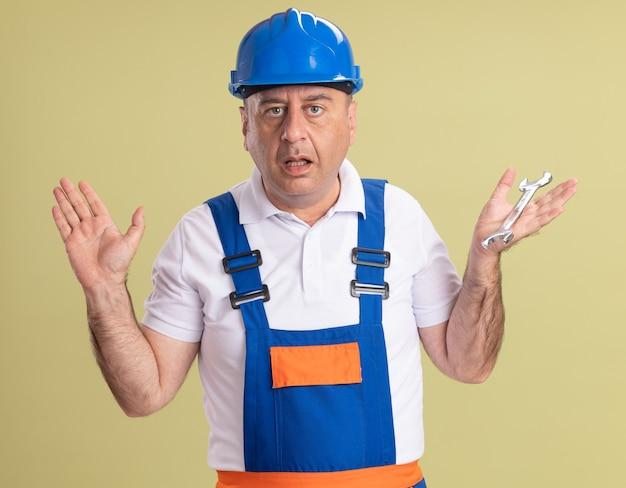 Ahnungsloser erwachsener baumeistermann in uniform steht mit erhobenen händen, die schraubenschlüssel lokalisiert auf olivgrüner wand halten