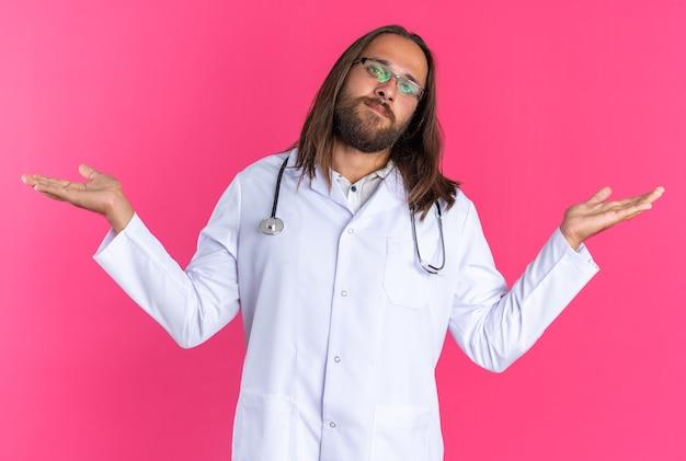 Ahnungsloser erwachsener männlicher arzt, der ein medizinisches gewand und ein stethoskop mit brille trägt und in die kamera schaut, die leere hände isoliert auf rosa wand zeigt
