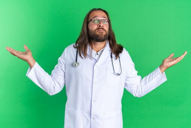 Ahnungsloser erwachsener männlicher arzt, der medizinisches gewand und stethoskop mit brille trägt und in die kamera schaut, die leere hände isoliert auf grüner wand zeigt