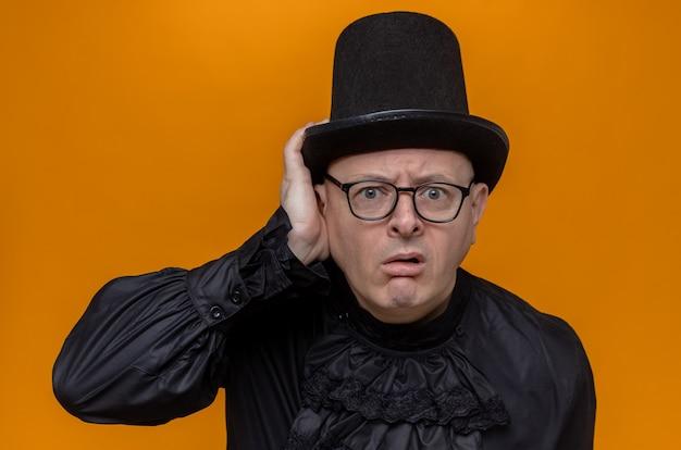 Ahnungsloser erwachsener mann mit zylinder und brille in schwarzem gothic-hemd, der hand auf seinen hut legt und schaut