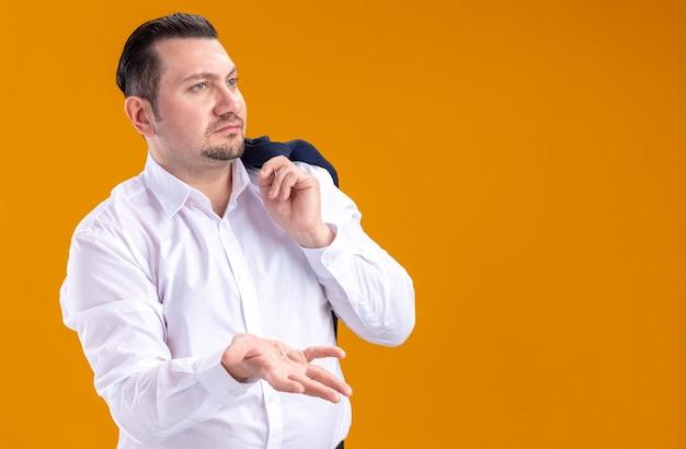 Ahnungsloser erwachsener slawischer geschäftsmann, der jacke auf seiner schulter hält und mit seiner hand auf die seite zeigt