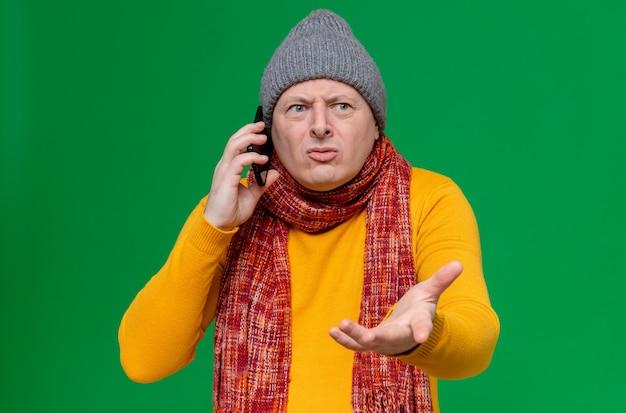 Ahnungsloser erwachsener slawischer mann mit wintermütze und schal um den hals, der am telefon spricht