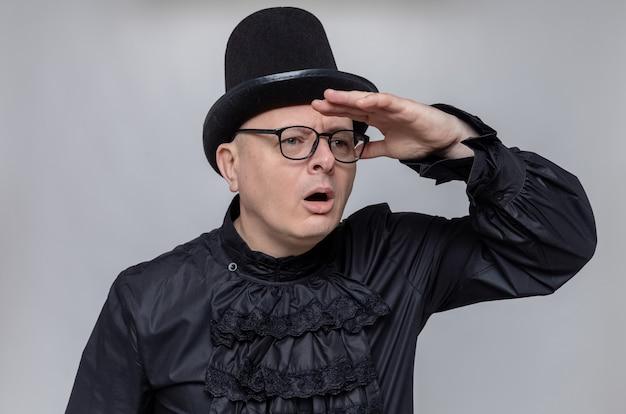 Ahnungsloser erwachsener slawischer mann mit zylinder und brille in schwarzem gothic-hemd, der die handfläche an seiner stirn hält und zur seite schaut