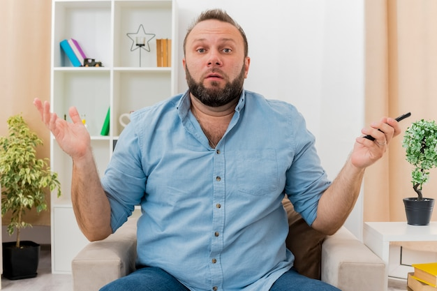 Ahnungsloser erwachsener slawischer mann sitzt auf sessel und hält fernbedienung fern im wohnzimmer